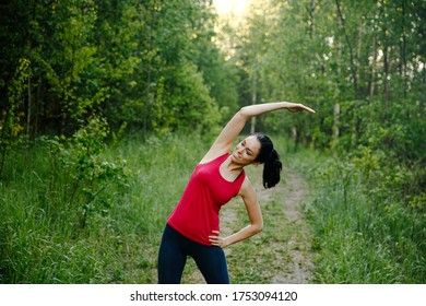 Beautiful girl stretches out in the woods on a dirt road before running