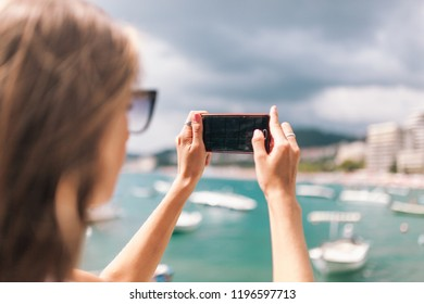 beautiful girl with a striped backpack takes pictures on the phone a beautiful landscape on the coast of Montenegro