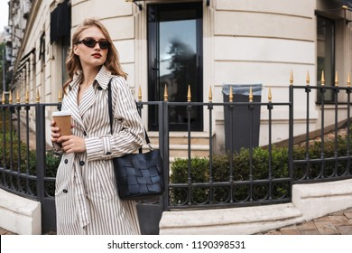 Beautiful girl in striped trench coat and sunglasses with black handbag holding coffee to go in hands thoughtfully looking aside walking around cozy city street