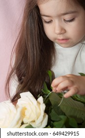 Beautiful girl stroking a bouquet of white roses