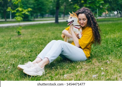 Beautiful girl student is hugging shiba inu puppy sitting on green lawn in park wearing casual clothes. Modern lifestyle, friendship and happiness concept.