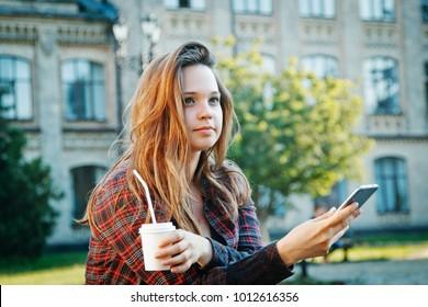beautiful girl student sitting on bench near university