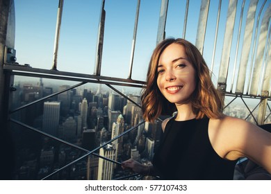 Beautiful girl student taking selfie photo with panoramic city view over New York, taken from Empire State Building, USA