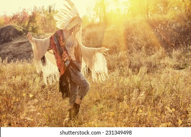 Beautiful girl in style of the American Indians dancing in the rays of the autumn sun. Western style. Jeans fashion.