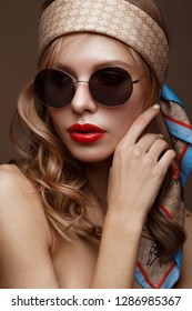 Beautiful girl in stylish clothes with sunglasses and red sexy lips. Beauty face. Photo taken in the studio