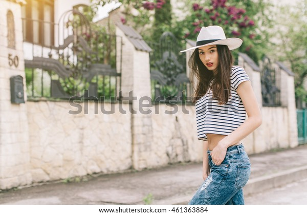 Beautiful girl in stylish jeans and white hat walking on the streets and happy.