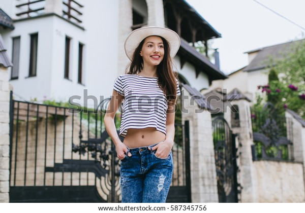 Beautiful girl in stylish jeans and white hat walking in the streets.