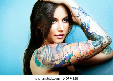 Beautiful girl with stylish make-up and tattooed arms. tattoo