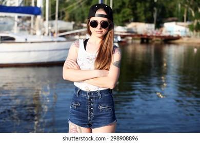 Beautiful girl with stylish make-up and tattooed body, outdoors
