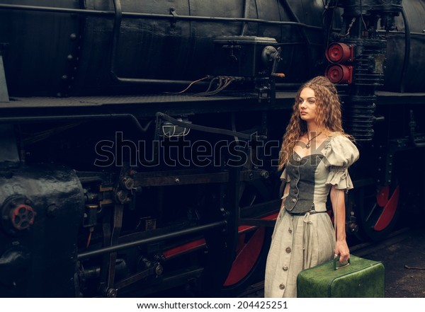 beautiful girl with a suitcase at a railway station