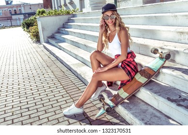 Beautiful girl in summer with board longboard skate sits telephone calls in social network conversation. Online application. Steps baseball cap tanned leather. Free space for text. Happy smiles.