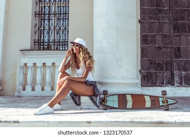 Beautiful girl in summer with board longboard skate phoning happy smiling. Online application video call to social networks. Emotions of joy and fun. Free space for text.