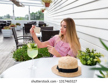 Beautiful girl in summer cafe. In hands of smartphone rings phone with headphones. Photographs and watches video over Internet. Video communication, call via social networks Internet application.