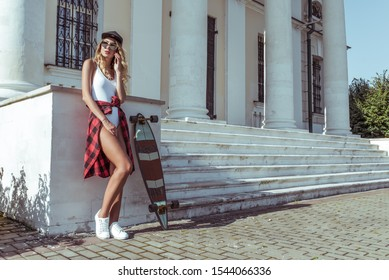 beautiful girl summer city, holding mobile phone, calls talks, listens audio message app Internet. Tanned figure, long hair sunglasses, skateboard. Free space text. Background building column stairs