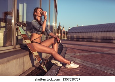 Beautiful girl in the summer city. Sits next to a longboard skateboard. Drinking coffee or tea from the mug. In his hand a smartphone. Free space for text.
