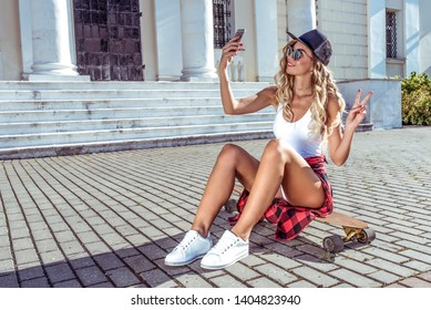 Beautiful girl in the summer city takes pictures on phone, free space, skate longboard. Happy smiling. The concept of fashion style, trends of youth, modern idea of clothing and leisure