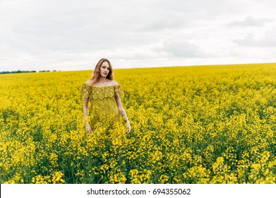 Beautiful girl in a summer dress among yellow flowers in a field
