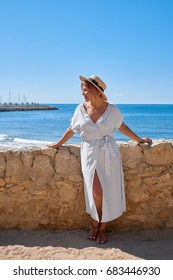 Beautiful girl in a summer dress and hat on the seashore near a background old city europe. Mediterranean Sea, Sitges, Spain.