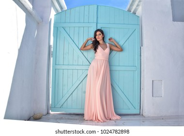 A beautiful girl in a summer dress on the terrace
