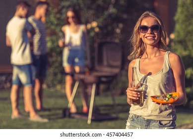 Beautiful girl in sun glasses is holding bottle of beverage and food, looking at camera and smiling while resting outdoors, her friends are talking in the background