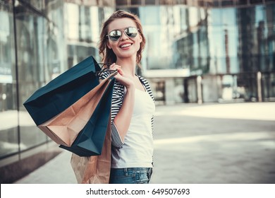 Beautiful girl in sun glasses is holding shopping bags, looking at camera and smiling while walking down the street
