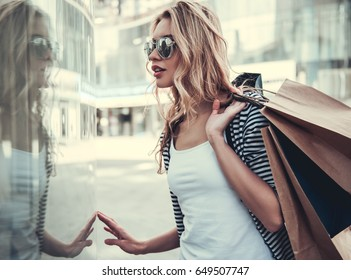 Beautiful girl in sun glasses is holding shopping bags, watching shop-windows and smiling while walking down the street