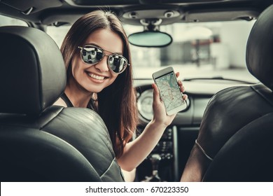 Beautiful girl in sun glasses is showing a smart phone with digital map, looking at camera and smiling while sitting in her car