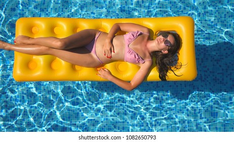 Beautiful girl in sunglasses and bikini lying on yellow inflatable mattress in swimming pool. Young tanned woman relaxing in basin of hotel on sunny day. Concept of summer vacation. Top view Close up.