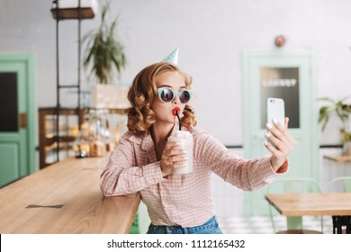 Beautiful girl in sunglasses and birthday cap sitting at the bar counter and drinking milkshake while taking cute photos on her cellphone in cafe