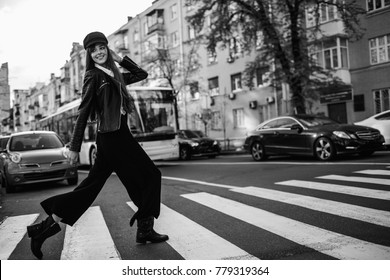 Beautiful girl with sunglasses. A model in a stylish wide-brimmed hat at a pedestrian crossing. Harmoniously similar clothes in gray tones. Street style shooting. Women's fashion.