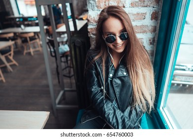 Beautiful girl in sunglasses posing on camera near window