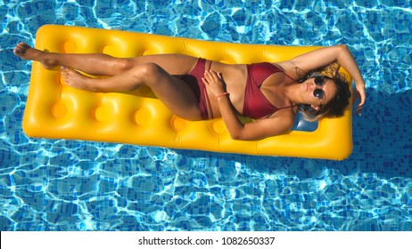 Beautiful girl in sunglasses and red bikini lying on yellow inflatable mattress in swimming pool. Young tanned woman relaxing in basin of hotel on sunny day. Concept of vacation. Top view Close up.