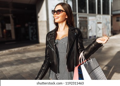 Beautiful girl in sunglasses walking after shopping, holding shopping bags, and smiling outdoors