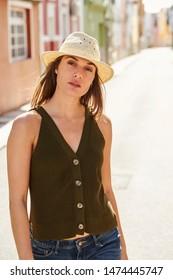 Beautiful girl in sunhat standing in street, portrait