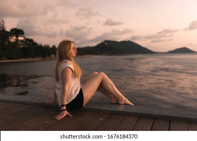 Beautiful girl at sunset on the sea in Thailand. Bright orange and yellow pink sky. Girl traveler enjoys the view. Woman in the tropics