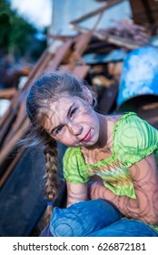 Beautiful girl at sunset, in a scrap heap, around a rusty metal.Braid hair