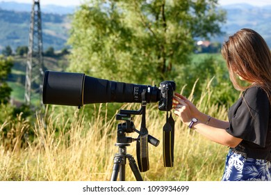 beautiful girl with super SLR camera and long lens