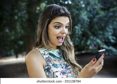 Beautiful girl surprised watching mobile phone
