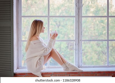 A beautiful girl in a sweater sits on a window sill and drinks coffee / copy space