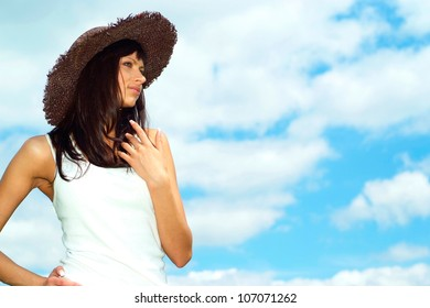 Beautiful girl with a sweet expression on her  face against the blue sky with clouds