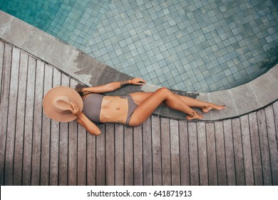 Beautiful girl swim into the pool. Fashion girl on the relax. The girl lies in a swimsuit and hat