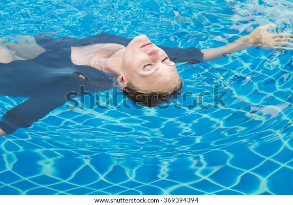 the beautiful girl swims in pool, in a black dress, quiet, happy and surprising, floats on water.