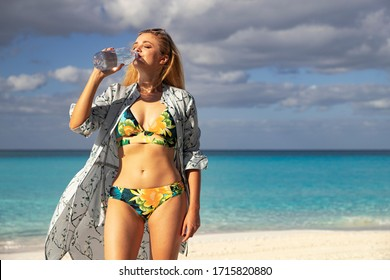 Beautiful girl in a swimsuit drinks water. Woman with a bottle of water at the beach. Woman on the beach