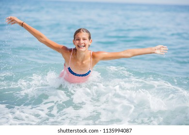 Beautiful girl in swimsuit having fun in the sea on tropical beach