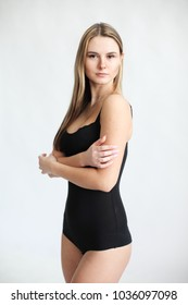 Beautiful girl in swimsuit posing against  grey white  background