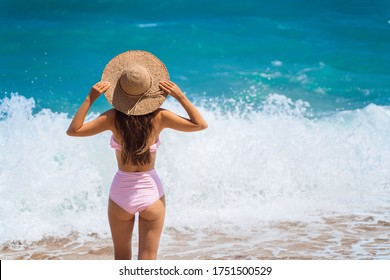 A beautiful girl in a swimsuit and a straw hat stands with her back to the camera against the background of a large azure ocean wave. The girl is enjoying a rest on the sandy beach. Tourist