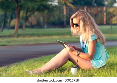 Beautiful girl with tablet in his hands. Woman relaxing on the nature. Beautiful toning.