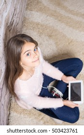 Beautiful girl with tablet. Modern learning, textbooks in electronic form on tablet. Girl listening to music on headphones. Electronic books, games on the tablet, shopping online. teen girl at home