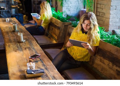 Beautiful girl with the tablet sits in a cafe