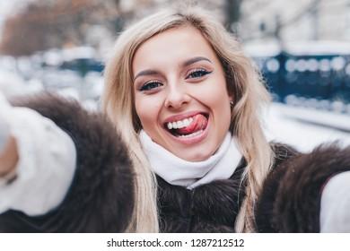 Beautiful girl takes funny winter selfie on city street